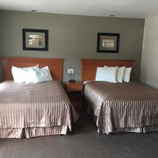 Two beds with striped sheets with a set of three pillows each